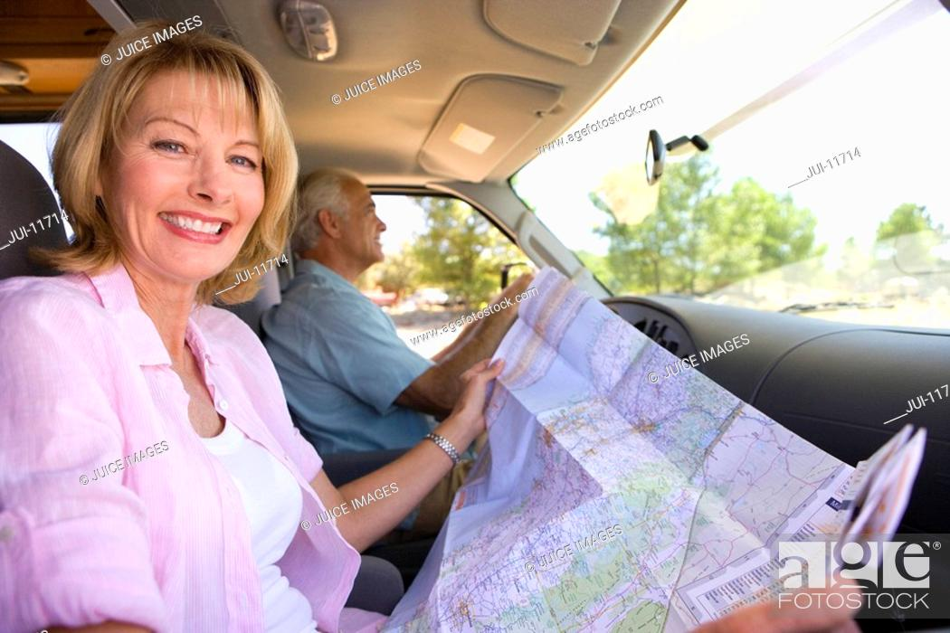 Stock Photo: Mature woman with map in motor home with husband, smiling, portrait.