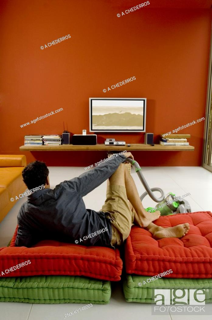 Stock Photo: Man watching TV lying on cushions, vacuum cleaner in front of him.