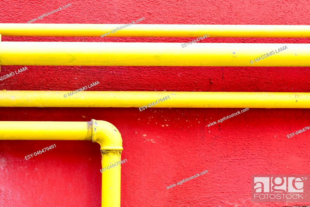 Stock Photo: yellow gas pipe on a pompeian red wall.