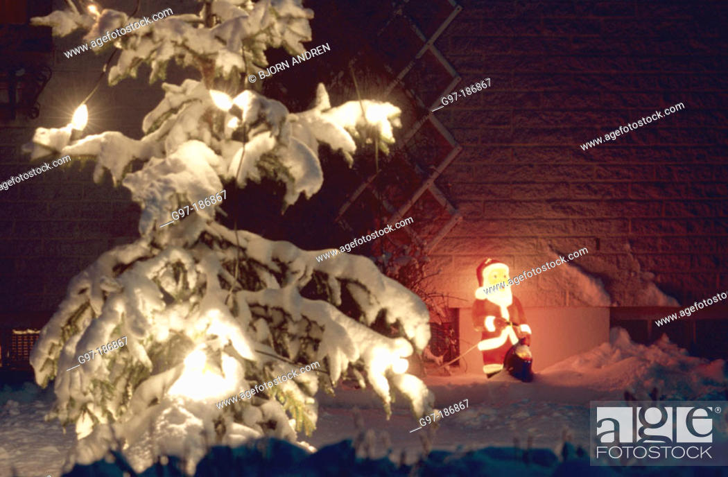 Stock Photo: Snow covered Christmas tree and lighted plastic Santa Claus. Sweden.