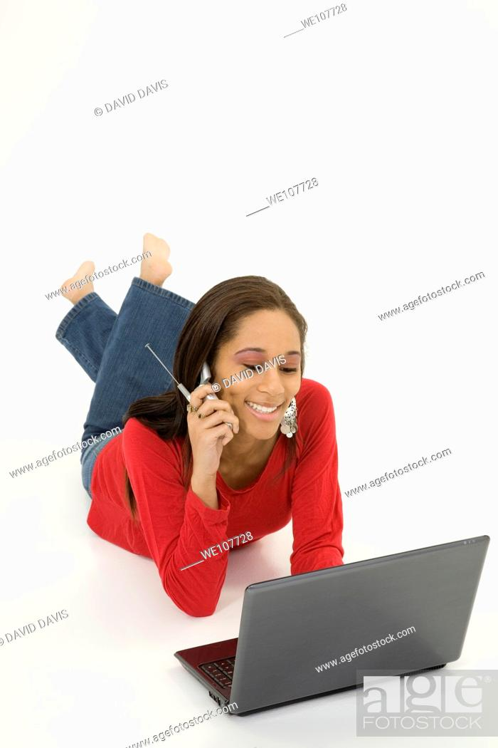 Stock Photo: African American teen working on laptop computer and talking ona cell phone.
