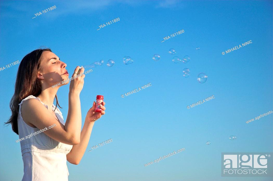 Stock Photo: Young woman blowing bubbles against blue sky, close-up.