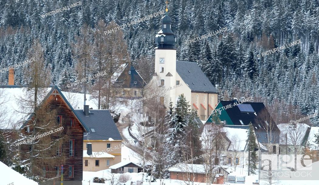 Stock Photo: 15 February 2021, Saxony, Kühnhaide: The church and houses of Kühnhaide, a district of the Saxon town of Marienberg in the Erzgebirge district.