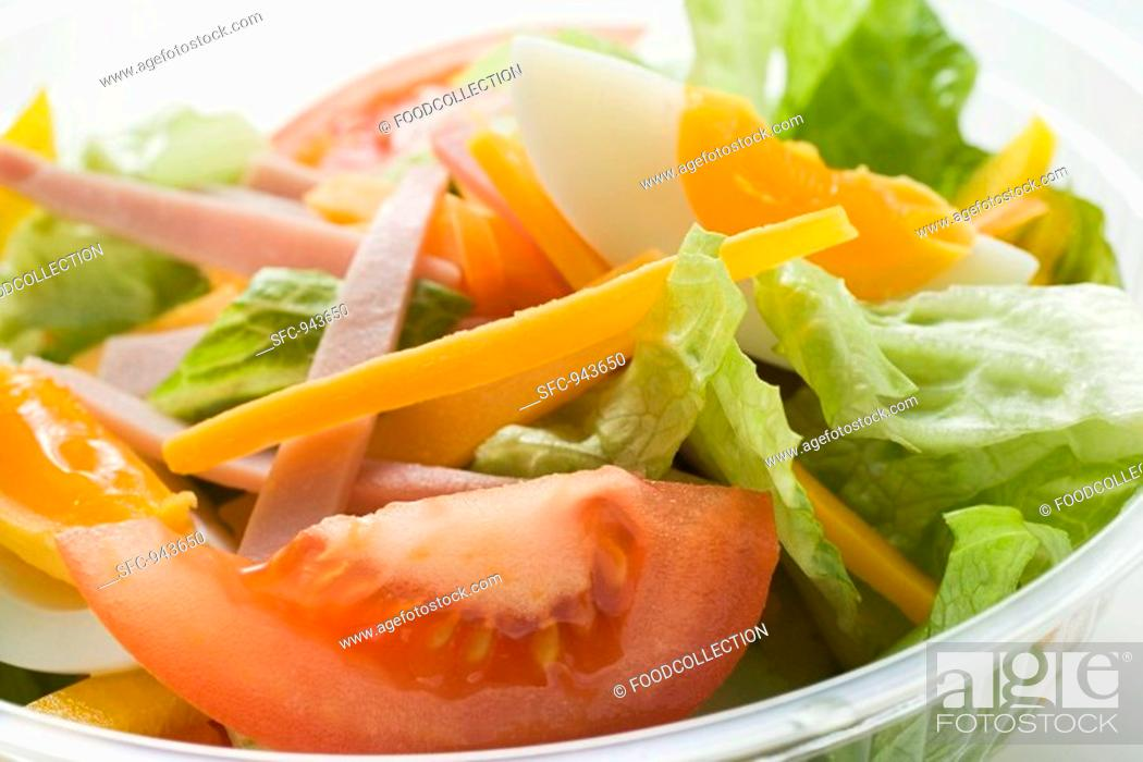 Stock Photo: Mixed salad with ham and egg in plastic container.