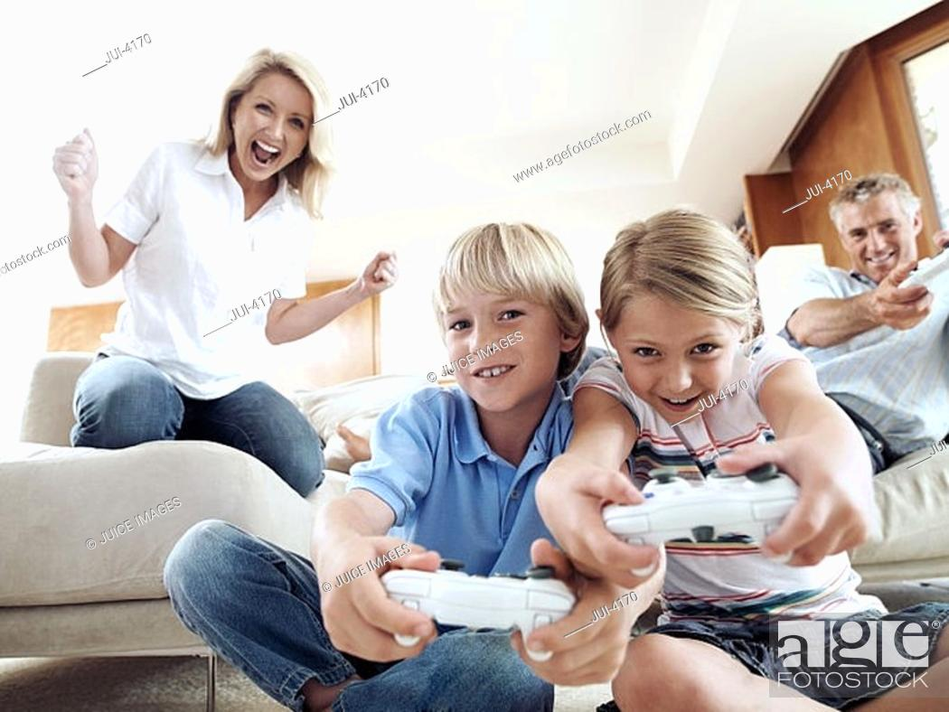 Stock Photo: Family playing with video games console at home, smiling, front view, low angle view.