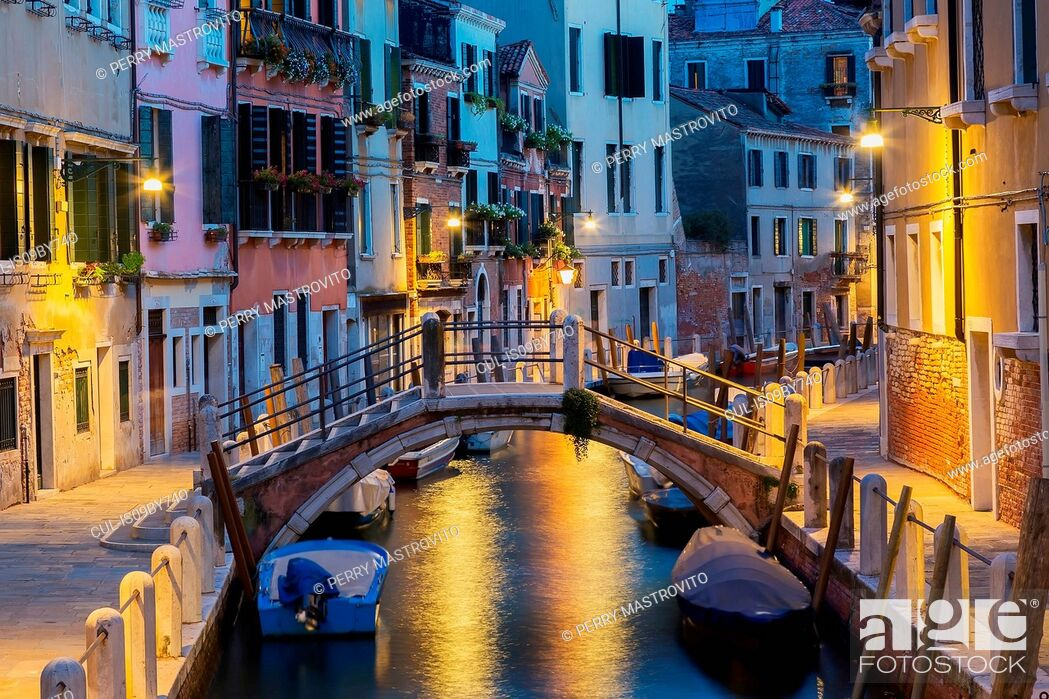 Stock Photo: Moored boats and footbridge over Rio de la Toletta Canal, old architectural style residential buildings at dusk, Dorsoduro district, Venice, Veneto, Italy.