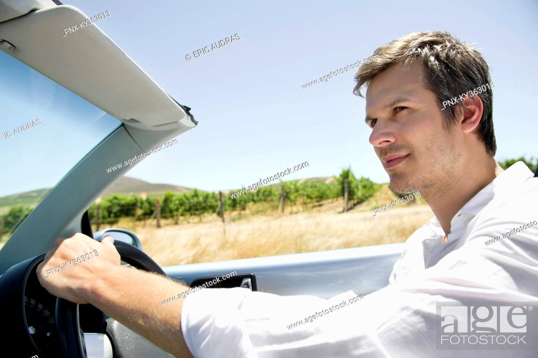 Stock Photo: Mid adult man driving a convertible car.