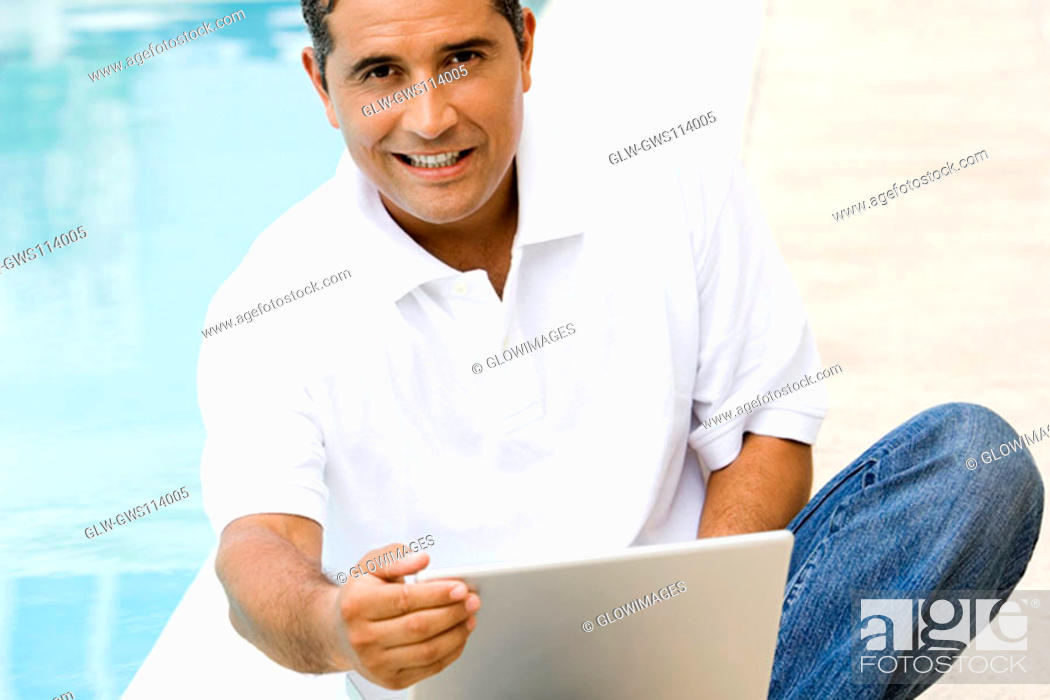 Stock Photo: Portrait of a mid adult man using a laptop.