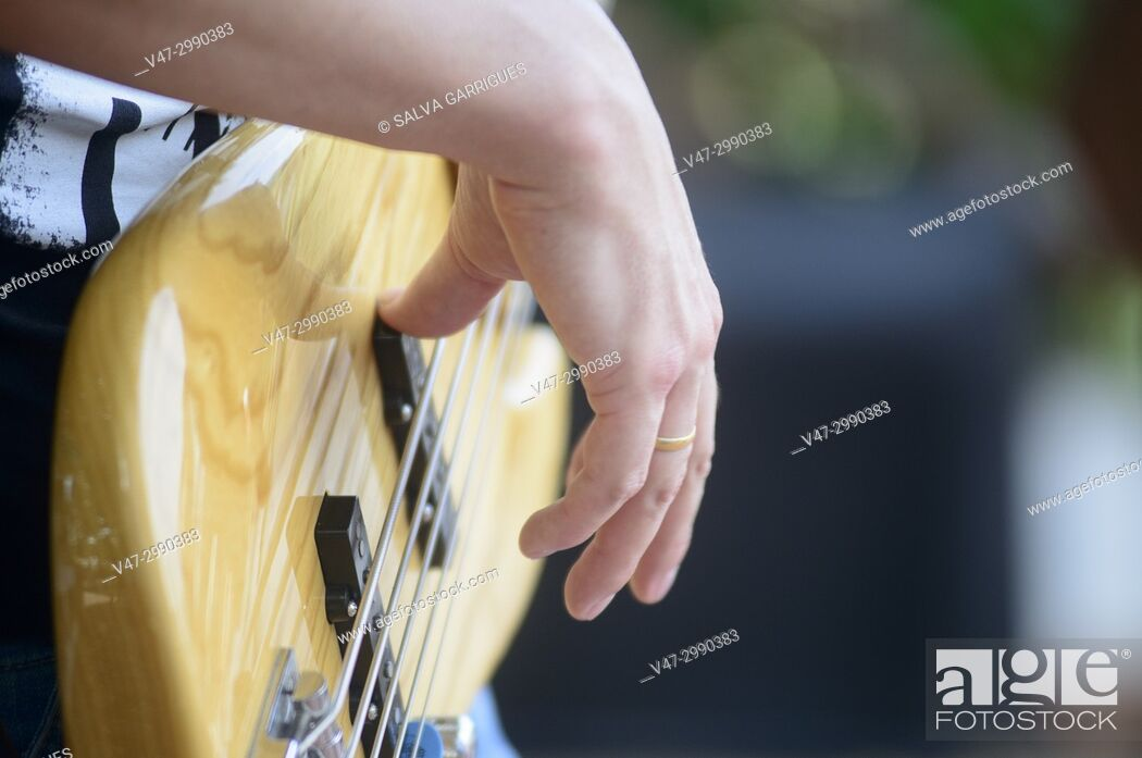 Stock Photo: Close-up of guitar and guitarist's hands at an outdoor concert.