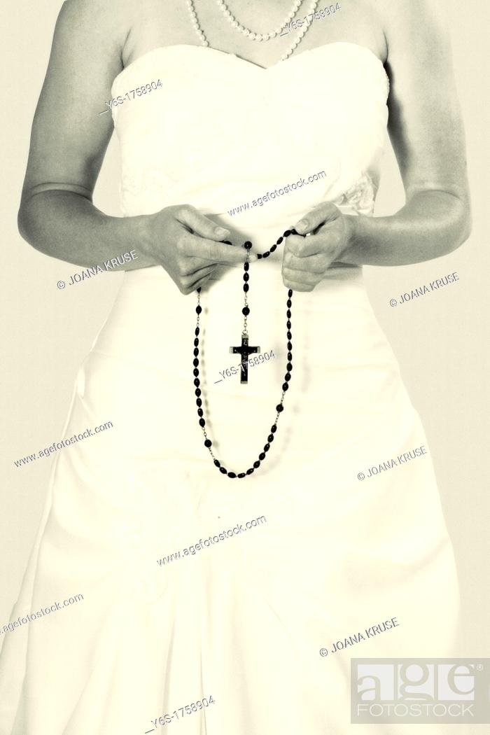 Stock Photo: a woman holding a rosary in her hands.