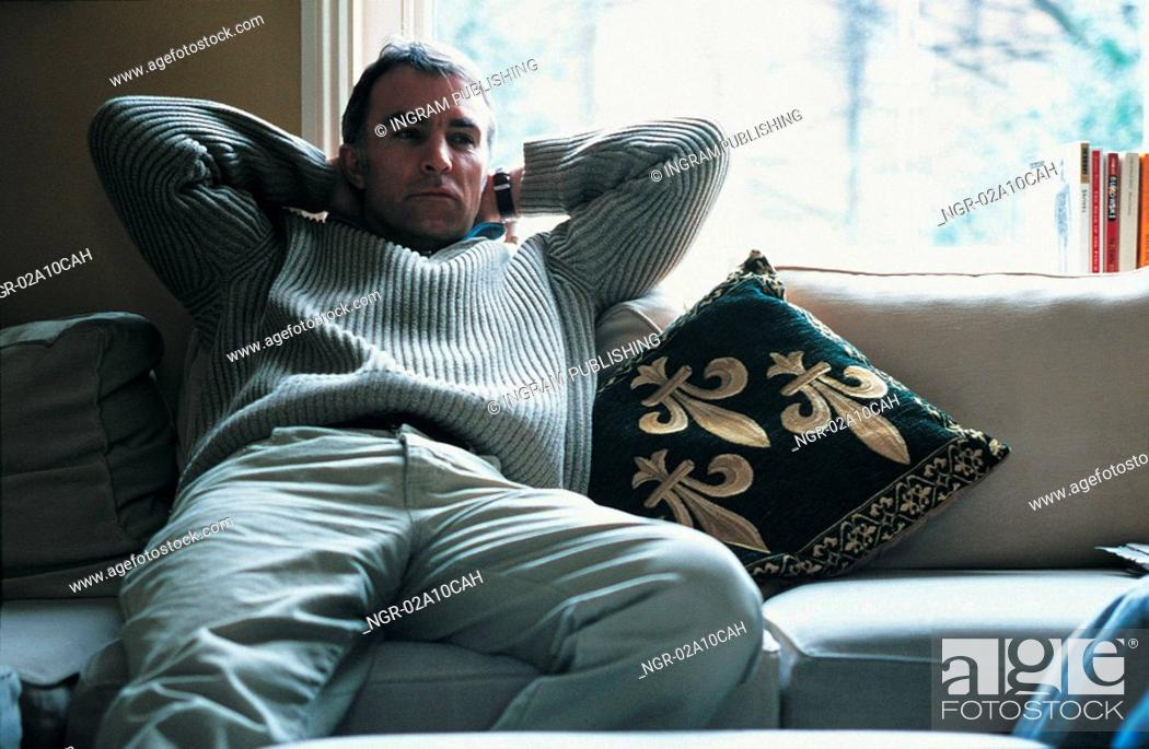 Stock Photo: elderly man sitting on a couch.