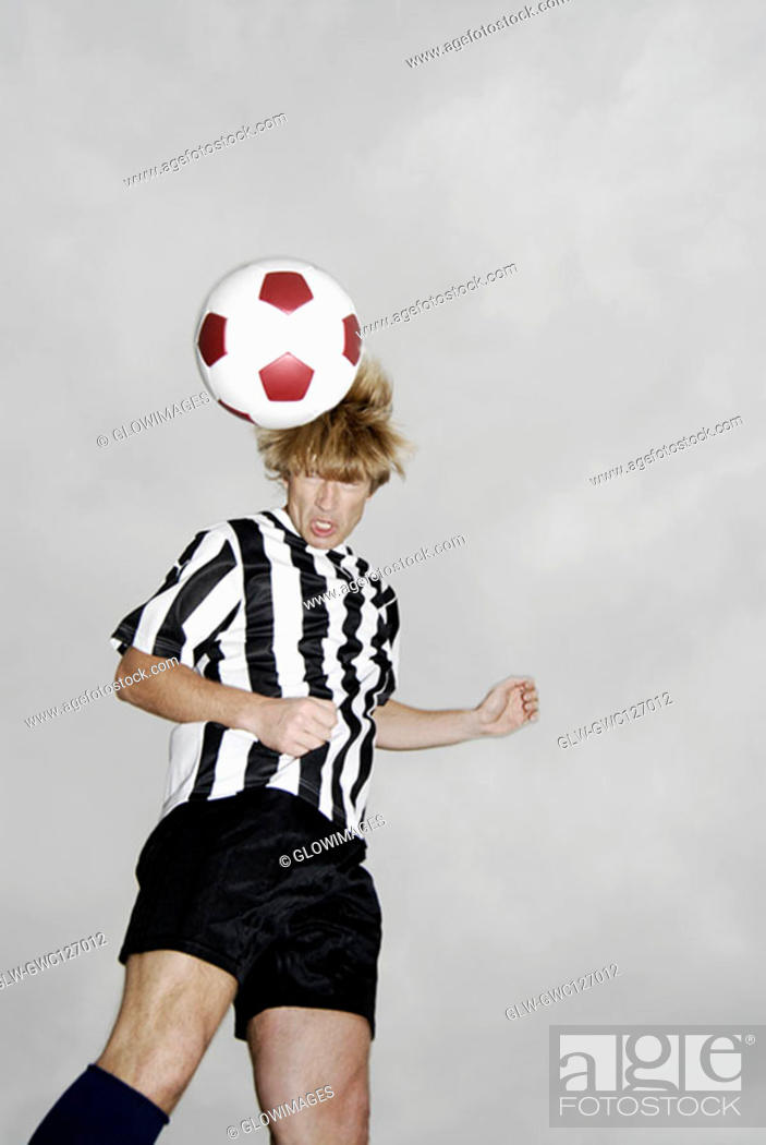 Stock Photo: Low angle view of a soccer player heading a soccer ball.