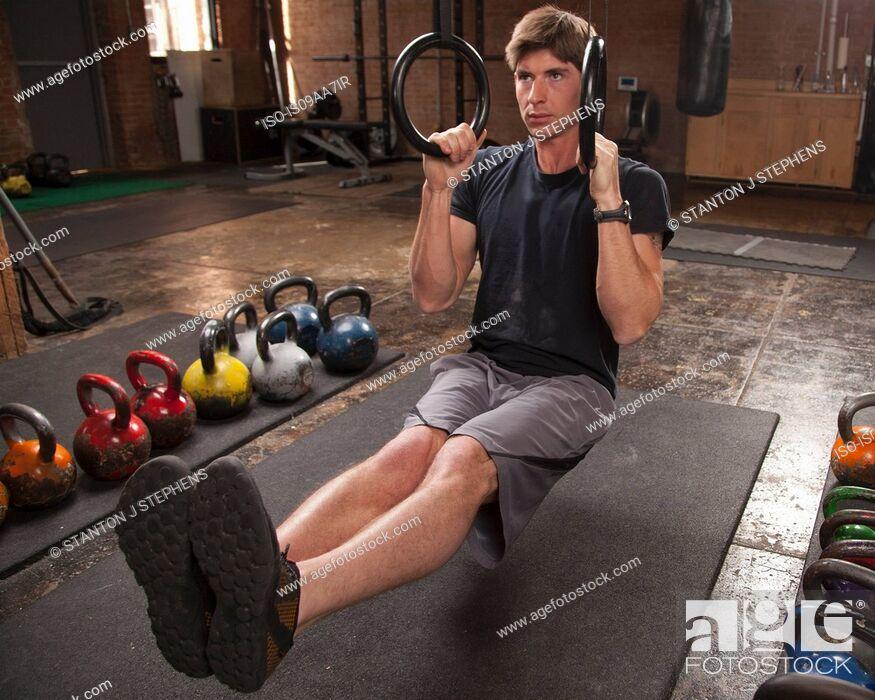 Stock Photo: Bodybuilder on gym floor using rings.