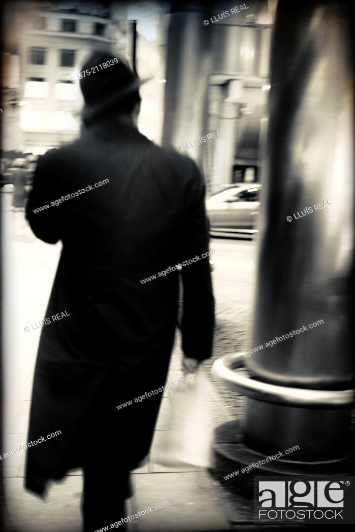 Stock Photo: Rear view of a unrecognizable man walking down the street and talking on the phone in London, England, UK, Europe.