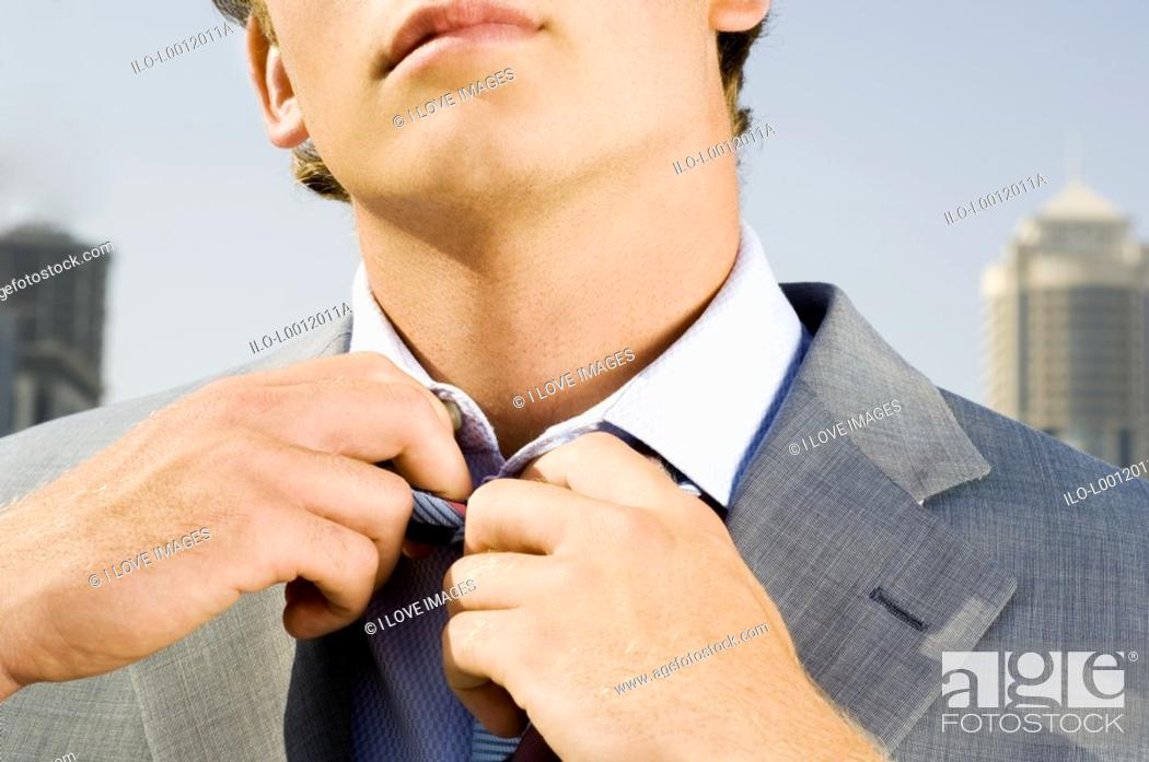 Stock Photo: A businessman adjusting his tie.