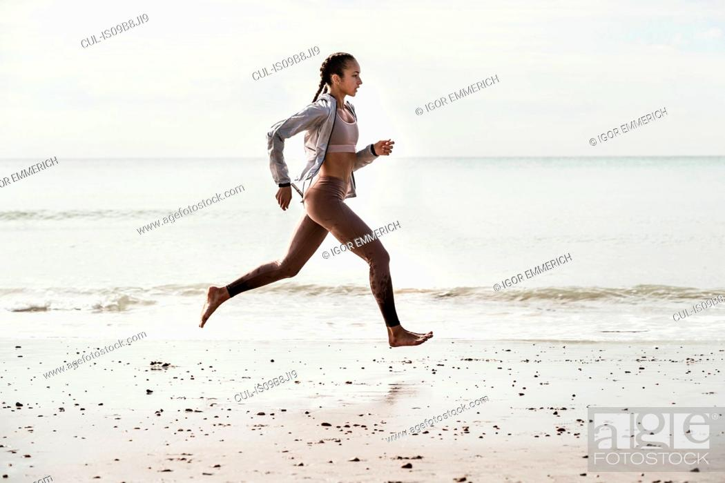 Stock Photo: Side view of young female runner running barefoot along water's edge at beach.