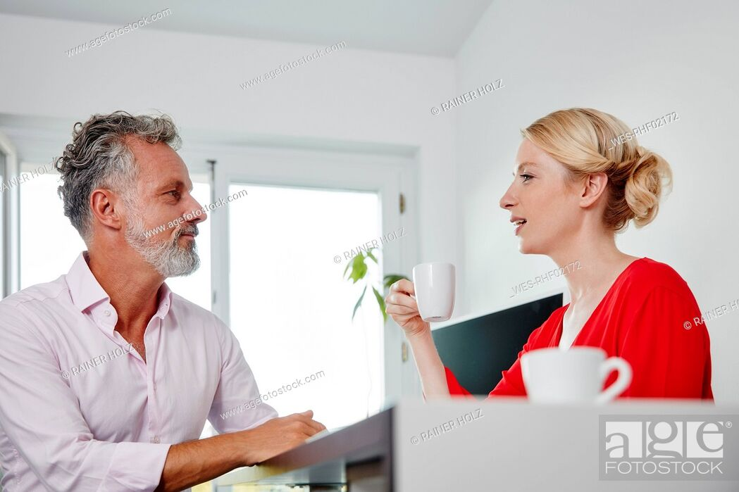 Stock Photo: Two colleagues with coffee cups talking in office.