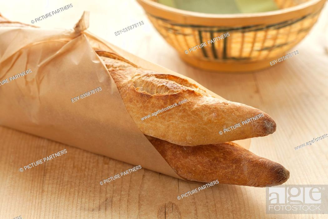 Stock Photo: Two French baguettes parisienne wrapped in paper.
