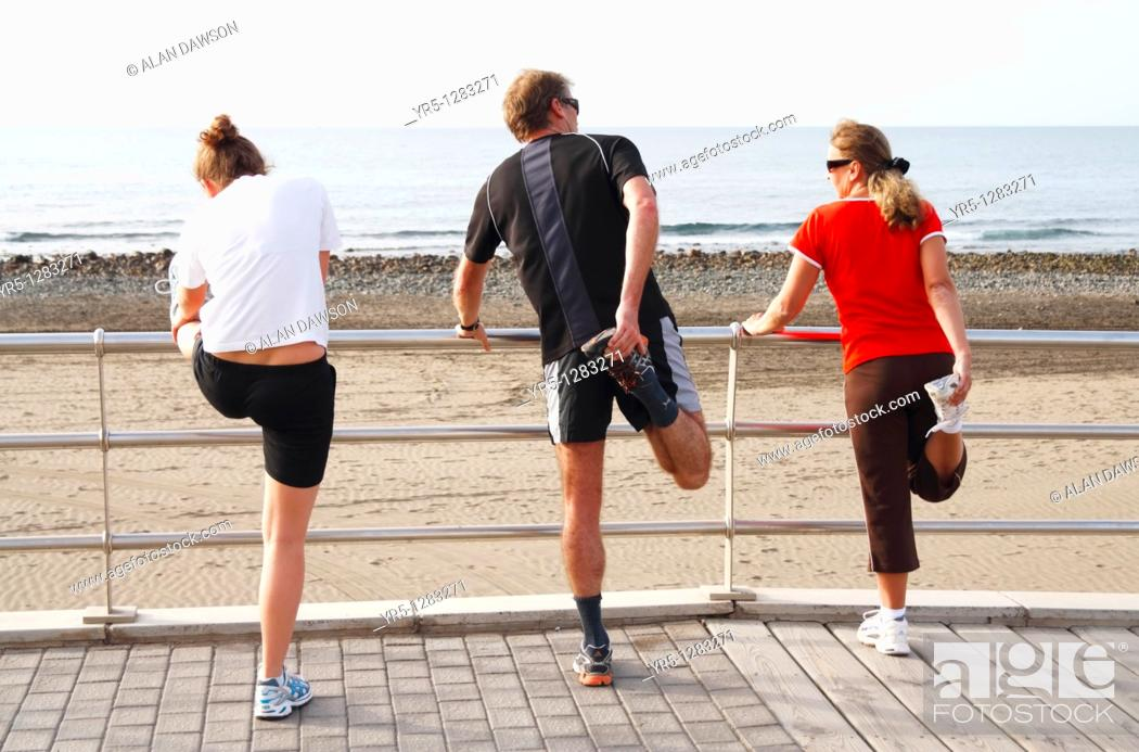 Stock Photo: People stretching before running on beach in Spain.