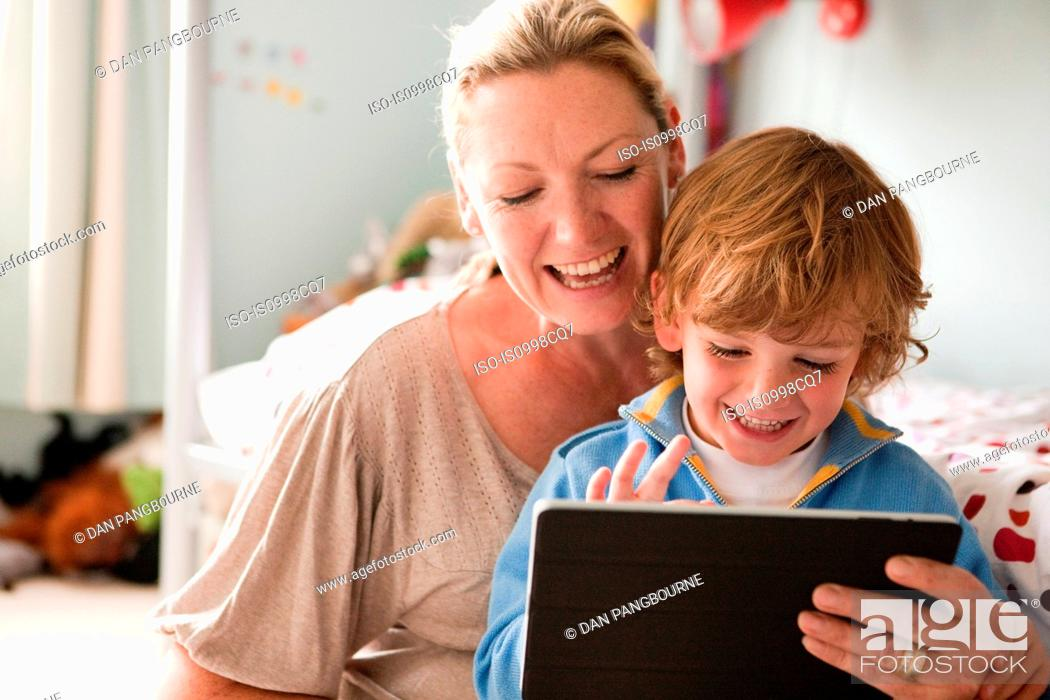 Stock Photo: Mother using a digital tablet with her son.