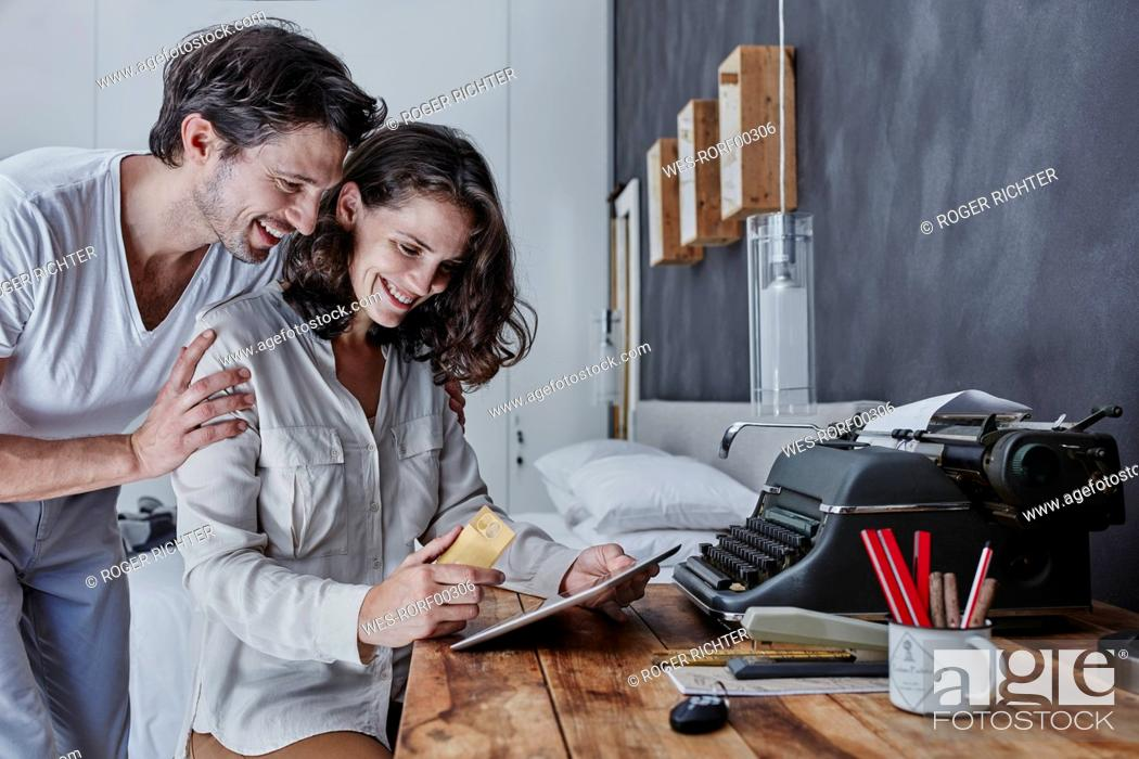 Stock Photo: Smiling couple shopping online in bedroom.