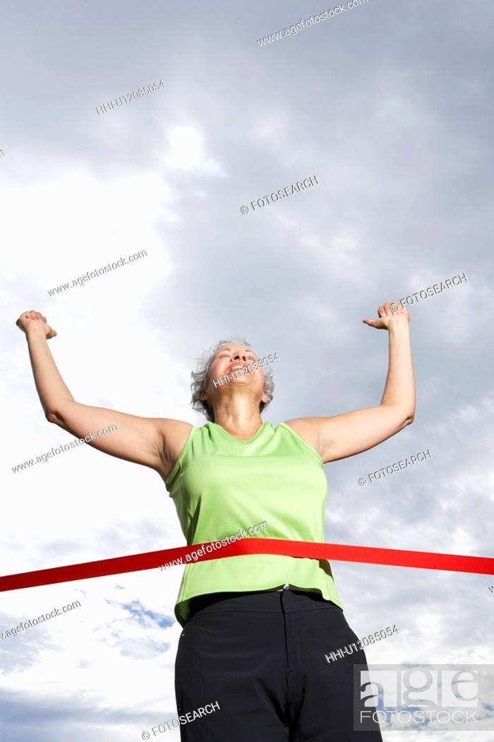 Stock Photo: Female runner crossing finishing line (low angle view).
