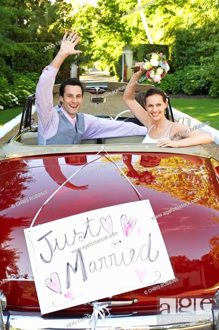 Stock Photo: Mid adult bride and groom in retro car waving hands.