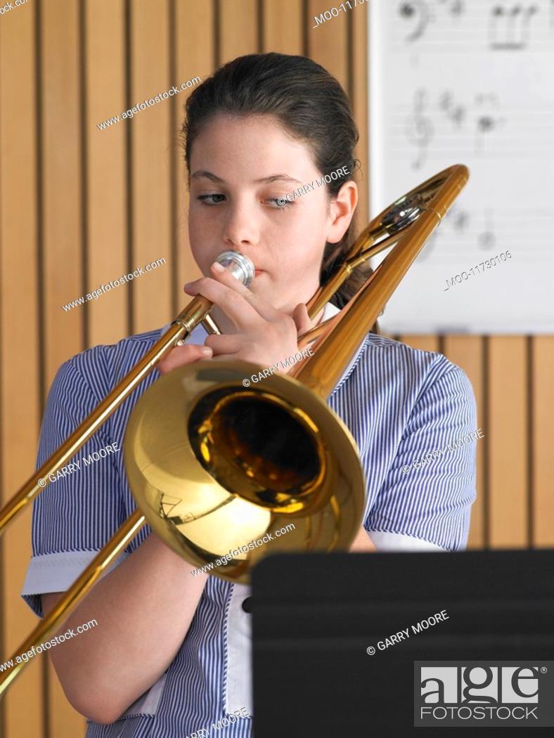 Stock Photo: High school girl playing trombone in class portrait.