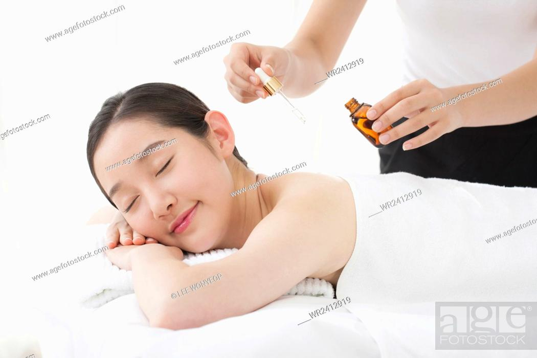Stock Photo: Side view portrait of young smiling woman getting essential oil on her skin closing her eyes.