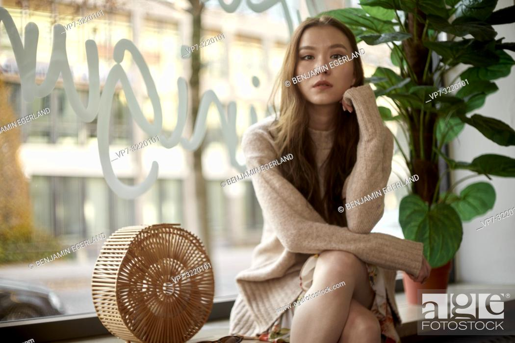 Imagen: fashionable young woman sitting indoors at shop window next to straw bag, individual style, in Munich, Germany.