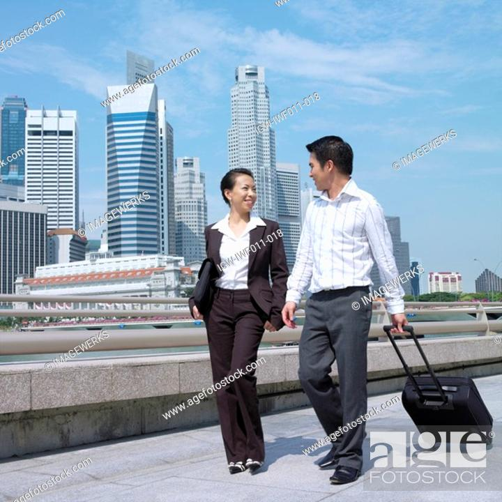 Stock Photo: Low angle view of a businesswoman talking to a businessman and pulling a suitcase.