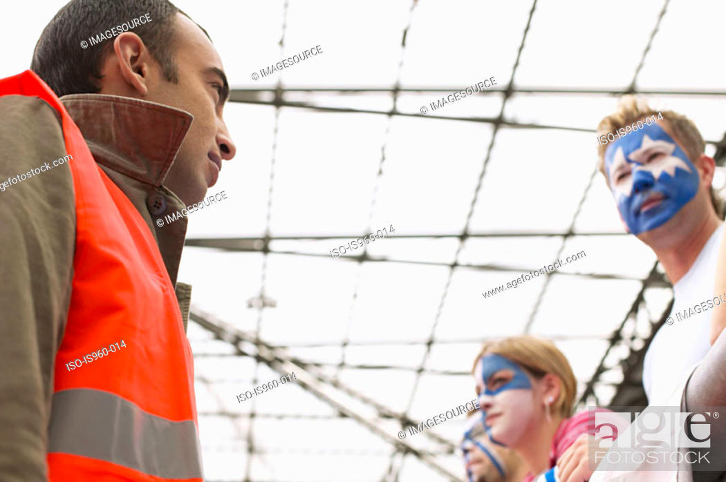 Stock Photo: Steward watching football supporters.