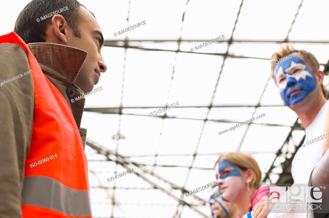 Stock Photo: Steward watching football supporters.