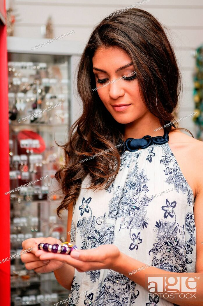 Stock Photo: Portrait of attractive young woman buying a bracelet at a jewelry.