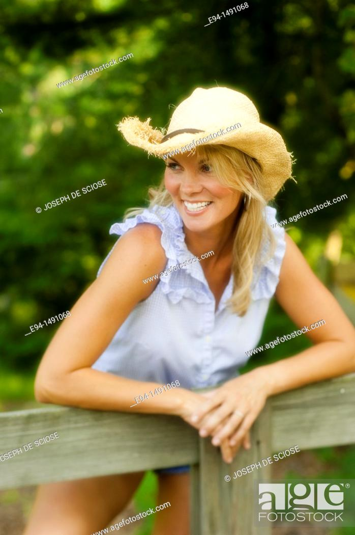 Stock Photo: Portrait of a 35 year old blond woman with a straw hat leaning over a wooden rail fence in a country setting.
