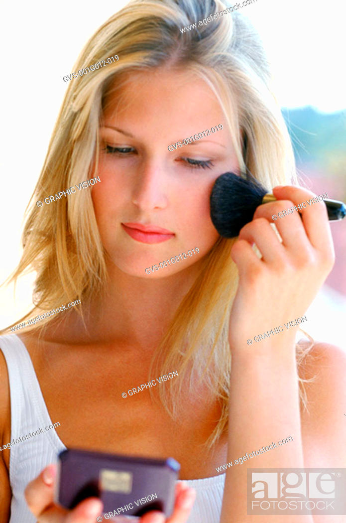 Stock Photo: Young woman applying makeup with a brush.
