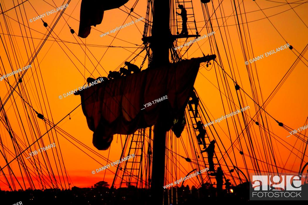 Stock Photo: Sailors Take Down the Sails on an Old Ship at Sunset.