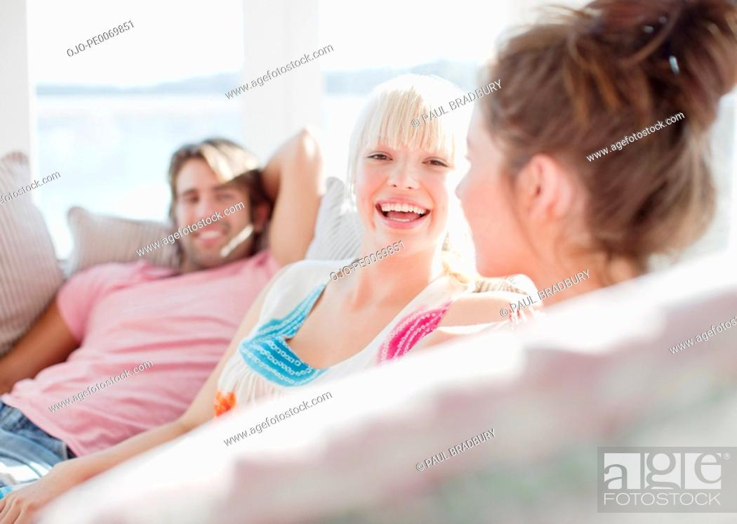 Stock Photo: Friends laughing on sofa.