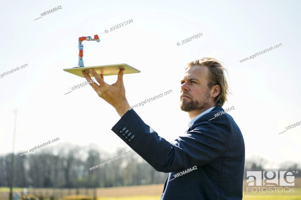Stock Photo: Male engineer looking at small robotic arm on digital tablet against clear sky during sunny day.