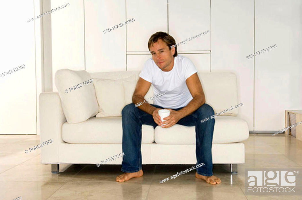 Stock Photo: Portrait of a young man sitting on a couch.