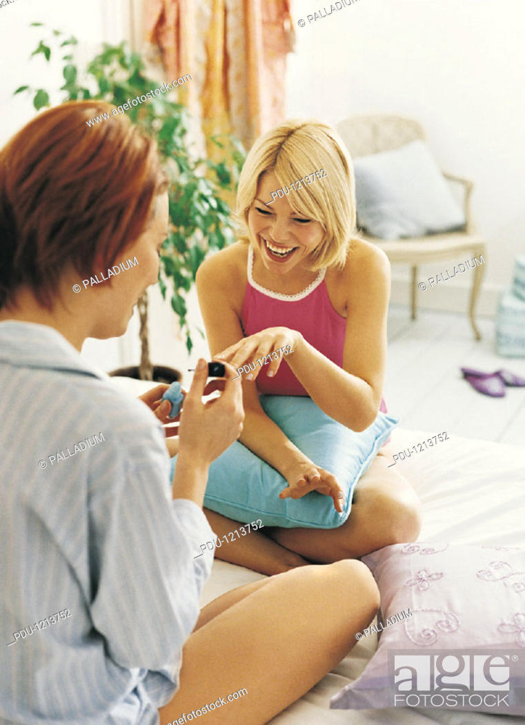 Stock Photo: Two Female Teenagers Applying Nail Varnish in Bed.
