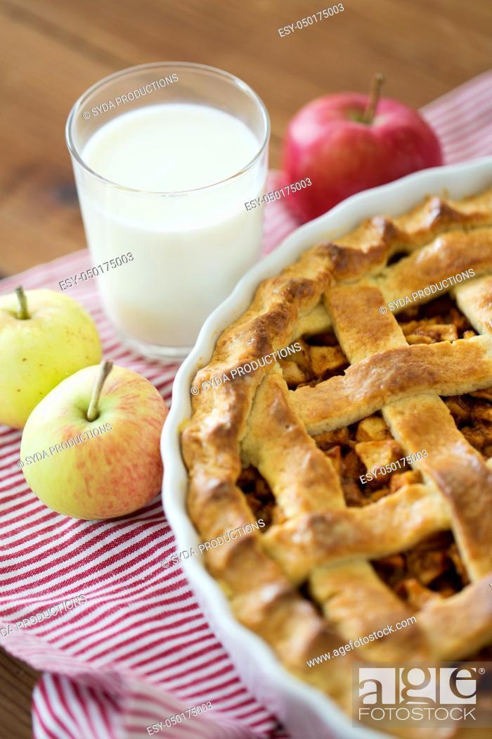 Stock Photo: apple pie in baking mold on wooden table.