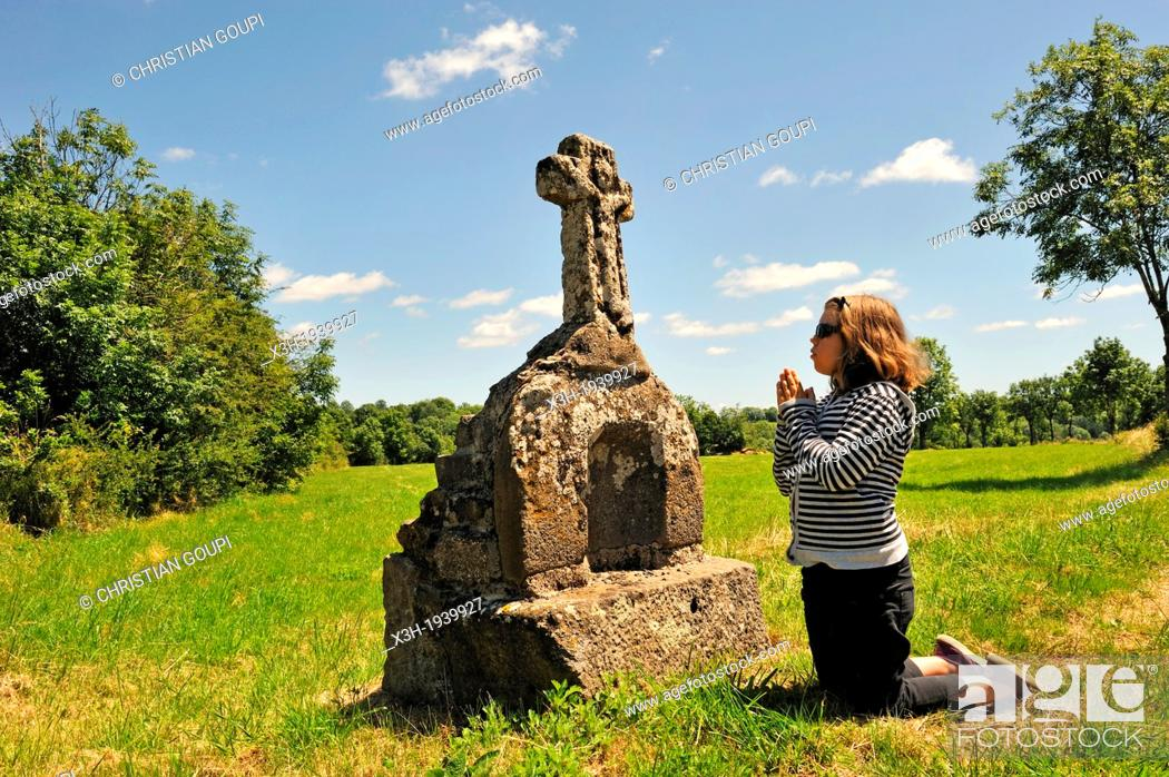 Stock Photo: little girl in meditation in front of a stone cross, Cantal department, Auvergne region, France, Europe.