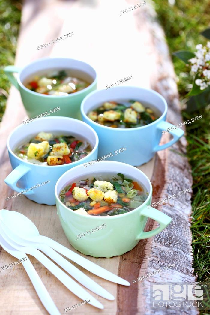 Stock Photo: Light vegetable and herb soup with croutons.