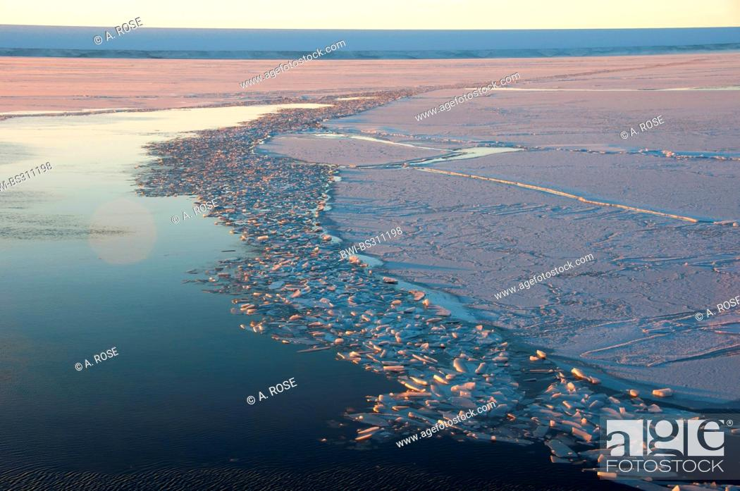 Imagen: waterway through the pack ice field opened by icebreakers at extreme frost near the iceberg resting place Austasen at sunrise, Antarctica.