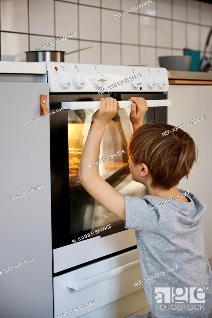 Stock Photo: Boy looking into oven.