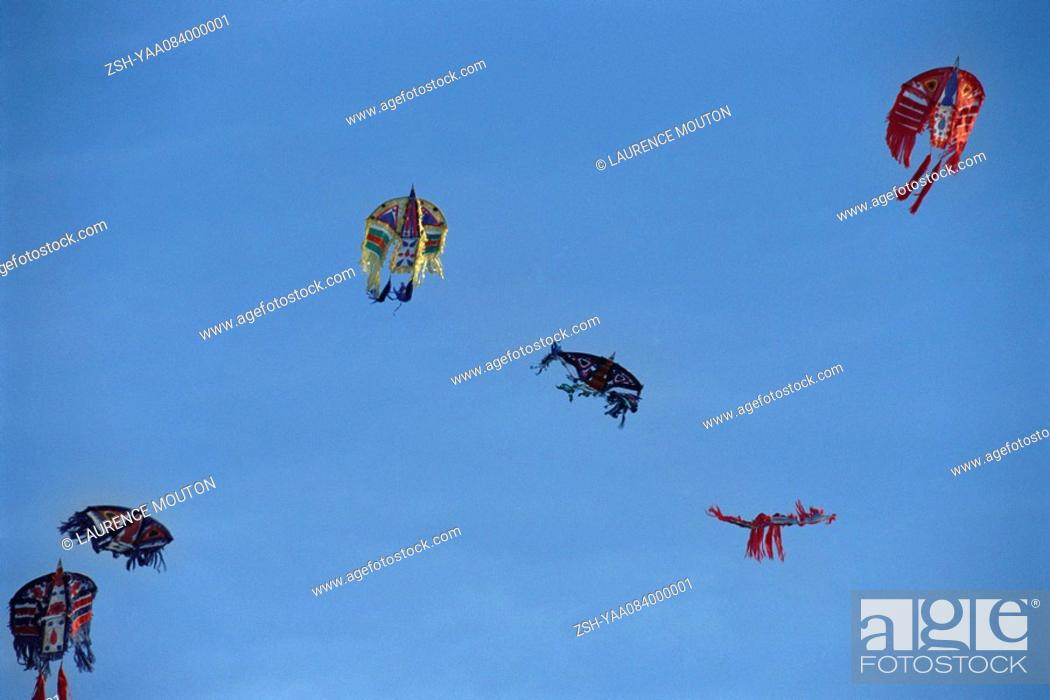 Stock Photo: Chinese kites flying high against clear blue sky.