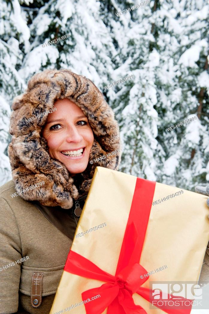 Stock Photo: Austria, Salzburg County, Mid adult woman standing with christmas parcel, smiling, portrait.