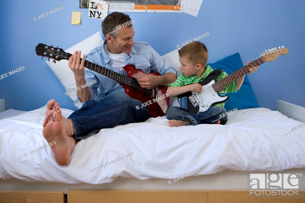 Stock Photo: Father and son 2-4 on bed with electric guitars, looking at each other.