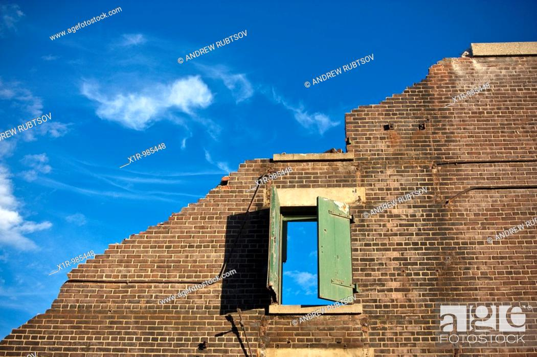 Stock Photo: Conceptual shot of a demolished building  Single wall remains with a window in it, blue skies and white clouds.